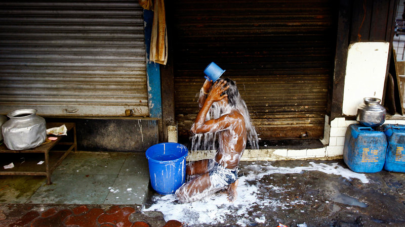 Man taking a bucket shower in India